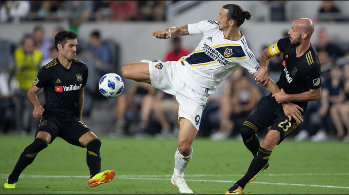 Los Angeles Galaxy forward Zlatan Ibrahimovic (9) fights for the ball against Los Angeles FC midfielder Benny Feilhaber (33) and defender Laurent Ciman (23) during the first half of a Major League Soccer match at Banc of California Stadium in Los Angeles, Calif. on Thursday July 26, 2018.  (Photo by Raul Romero Jr, Contributing Photographer)